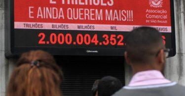 Pessoas observam painel eletrônico da Associação Comercial de São Paulo, instalado no centro da cidade, que indica a arrecadação de 2 trilhões de reais de impostos em 2015 (Foto: Werther Santana/Estadão Conteúdo)